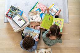 Zwei Kinder mit vielen Büchern